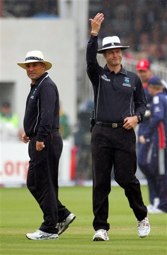 Umpires Simon Taufel, right, signals for the covers to be brought on during the fourth one-day international between England and South Africa at Lord's cricket ground on Sunday Aug 31, 2008.