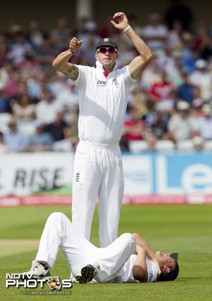 England's Jonathan Trott lies hurt after falling while fielding as teammate Kevin Pietersen calls for assistance on the second day of their cricket Test match against India at Trent Bridge. (AP Photo)