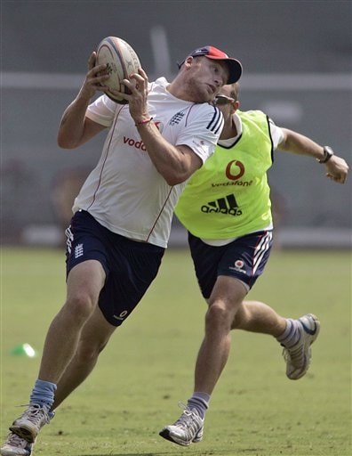 Andrew Flintoff (front) runs with a rugby ball as assistant coach Andy Flower chases him during a practice session in Mumbai on Saturday, November 8, 2008. (AP Photo)
