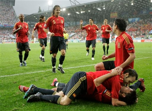 Spain's David Villa, on ground at right, is congratulated by teammate Andres Iniesta after Villa scored his team's 2nd goal, as the other team players run toward them during the group D match between Spain and Russia in Innsbruck, Austria.