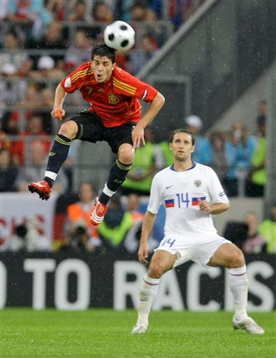 Spain's David Villa, left, heads a ball, as Russia's Roman Shirokov looks on during the group D match between Spain and Russia in Innsbruck, Austria.
