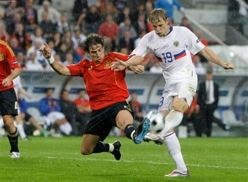 Spain's Carles Puyol, left, and Russia's Roman Pavlyuchenko challenge for the ball during the group D match between Spain and Russia in Innsbruck, Austria.