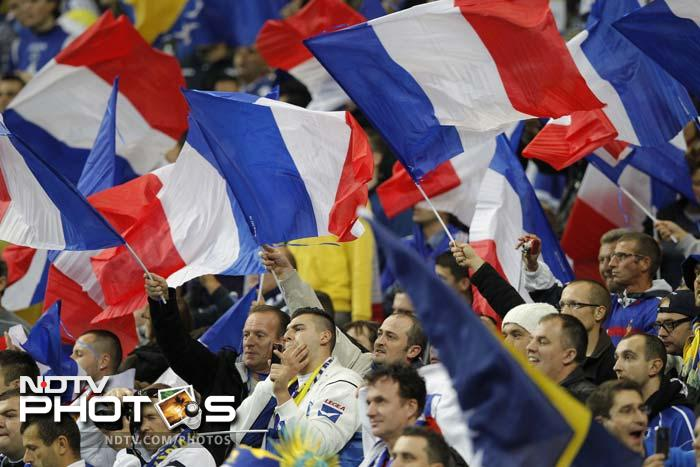 French fans wave France's national flags before the UEFA Euro 2012 Group D qualifying football match France vs. Bosnia-Herzegovina.