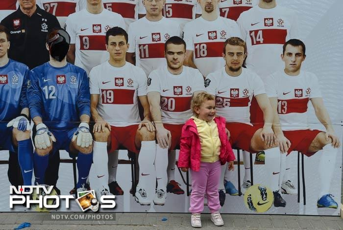 A child poses in front of a photo wall with Polish players prior to a training session of the Irish team at the Gdynia Arki stadium in Gdynia ahead of the Euro 2012 football championship. (AFP Photo)