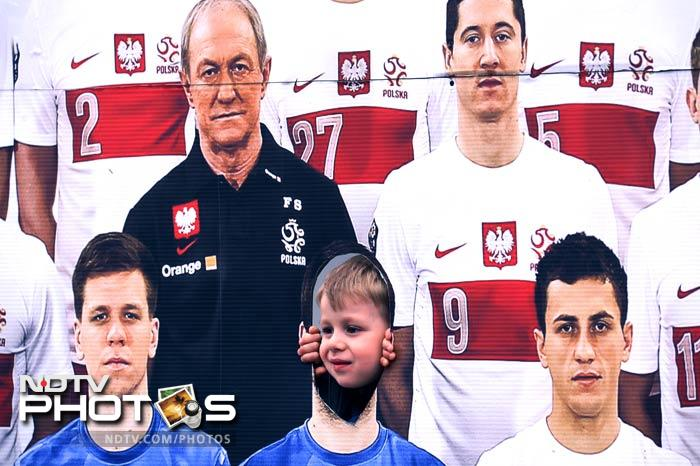 A young fan on a photo wall with Polish players prior to a training session of the Irish team at the Gdynia Arki stadium in Gdynia ahead of the Euro 2012 football championship. (AFP Photo)