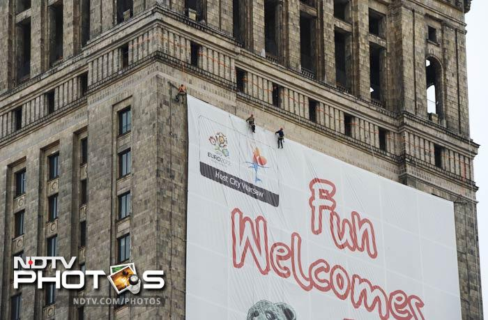 Workers fix a Euro 2012 football championships advertisement banner on the facade of a tower in Warsaw. (AFP Photo)