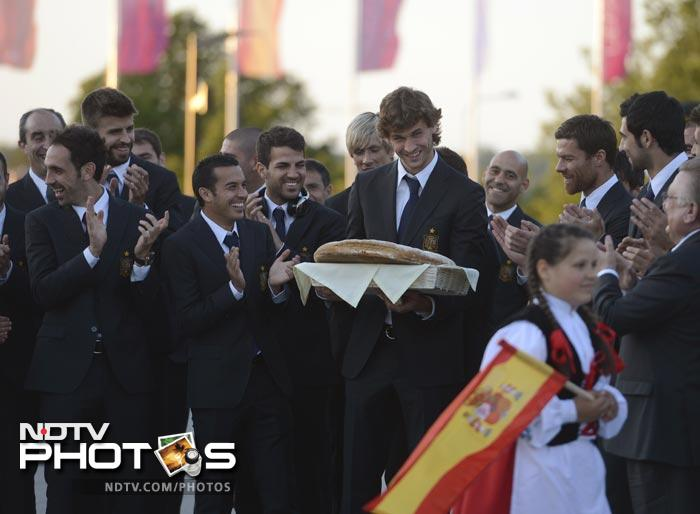 Spain Fernando Llorente (C) holds a bread as he is welcomed with teammates upon the Spanish team's arrival at their hotel in Gniewino on June 5, 2012 ahead of the Euro 2012 football championships. AFP PHOTO/ PIERRE -PHILIPPE MARCOU