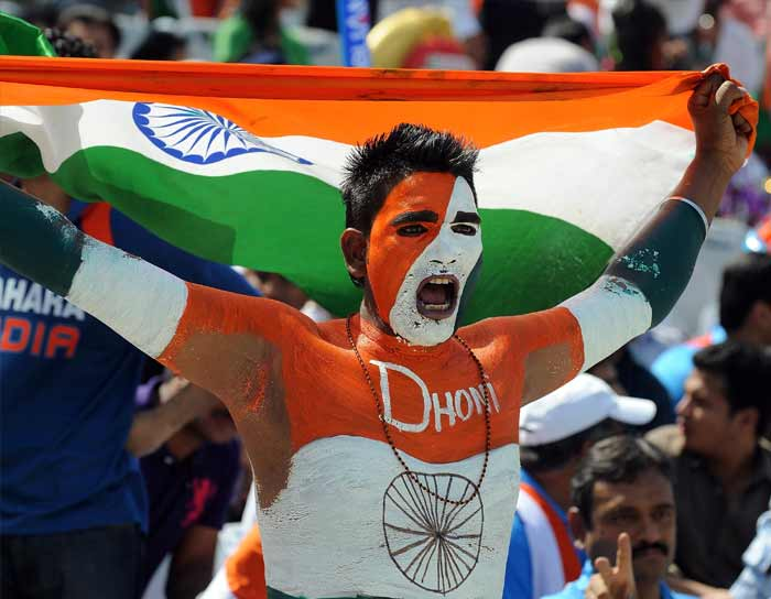 Just moments before the start of the high octane semi final clash between India and Pakistan, a fan, painted in the colours of the Indian national flag, cheers for team India. (AFP Photo)