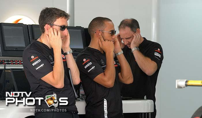 Hamilton and members of the McLaren team cover their ears against noise but somehow, at first glance, this appears like the Gandhi's teaching of don't see bad, do not hear bad and do not speak it, represented by three monkeys. No implications here though. (AFP image)