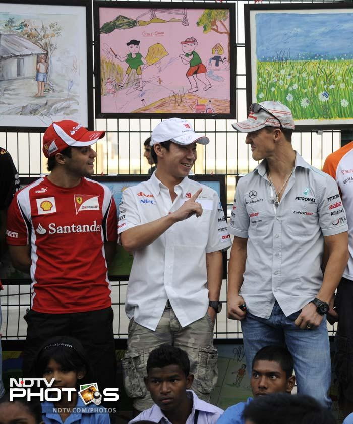 Others like Kamui Kobayashi (C), Felipe Massa (L) and Michael Schumacher also attended an exhibition of paitings made by local school-children. (AFP image)
