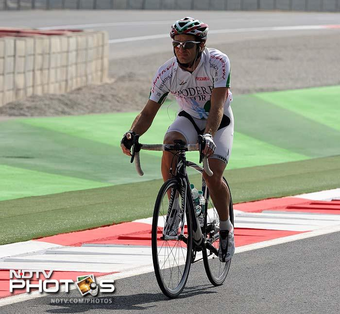 Still others had still other things to do. Team Lotus driver Jarno Trulli is seen here enjoying his cycle on the track. (AFP image)