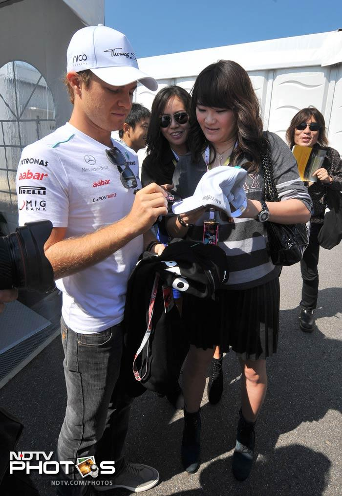 Mercedes-AMG driver Nico Rosberg of Germany (L) signs an autograph at the paddock just before the start of the Japanese Grand Prix.