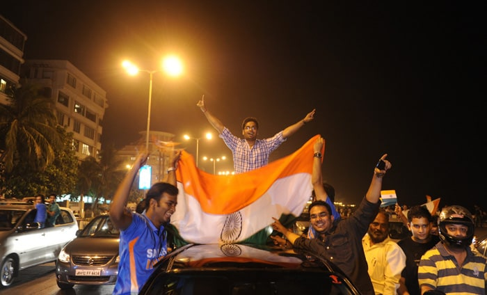 <b>Mumbai: </b>Indian fans hold a national flag as they celebrate India's victory over Pakistan. (AFP Photo)