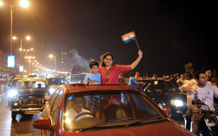 <b>Mumbai: </b>Indian fans ride in a car holding a national flag as they celebrate India's victory. (AFP Photo)