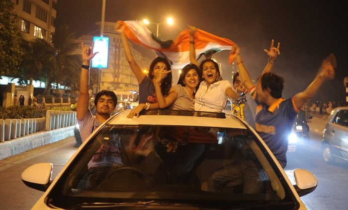 <b>Mumbai: </b>Indian fans ride in a car as they hold a national flag to celebrate India's victory. (AFP Photo)