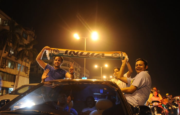 <b>Mumbai: </b>Indian fans ride in a car holding a national flag as they celebrate India's victory in a semi final. (AFP Photo)