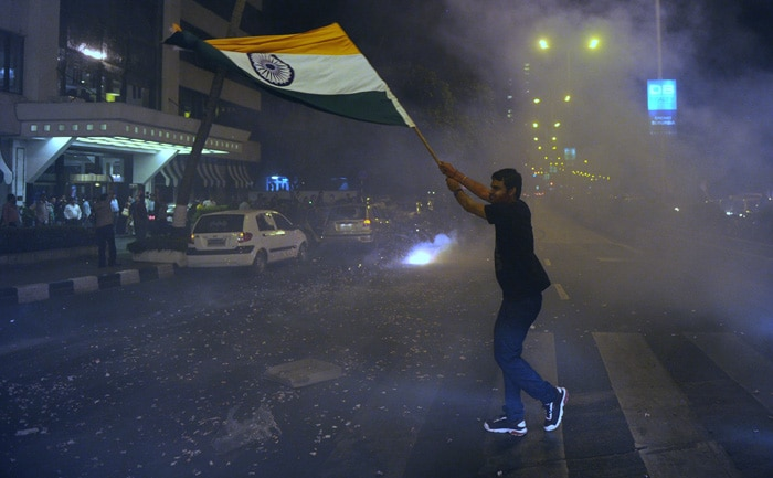 <b>Mumbai: </b>An Indian fan holds a national flag as he celebrates India's victory. (AFP Photo)