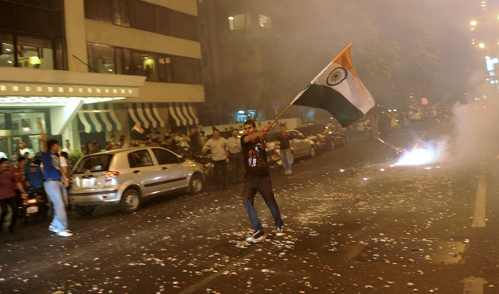 <b>Mumbai: </b>An Indian fan holds a national flag as he celebrates India's victory in a semi final of the Cricket World Cup 2011 match against Pakistan. (AFP Photo)