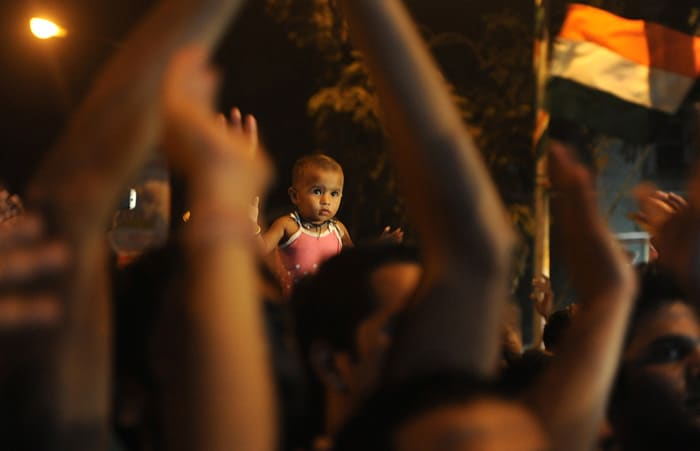 <b>Mumbai: </b>A child looks on as Indian fans celebrate India's victory in semi-final match against Pakistan. (AFP Photo)