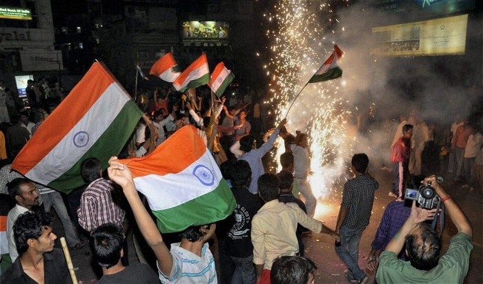 "<b>Jharkhand: </b>Indian fans celebrate the team's victory over Pakistan in the Cricket World Cup semifinal match, in front of captain Mahendra Singh Dhoni's house ""Shourya"" in Ranchi. (PTI Photo)"
