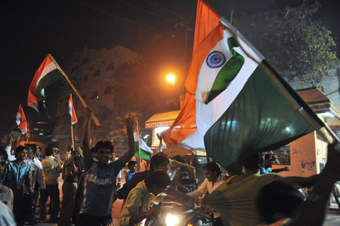 <b>Hyderabad: </b>Indian cricket fans celebrate by waving flags in a street. (AFP Photo)