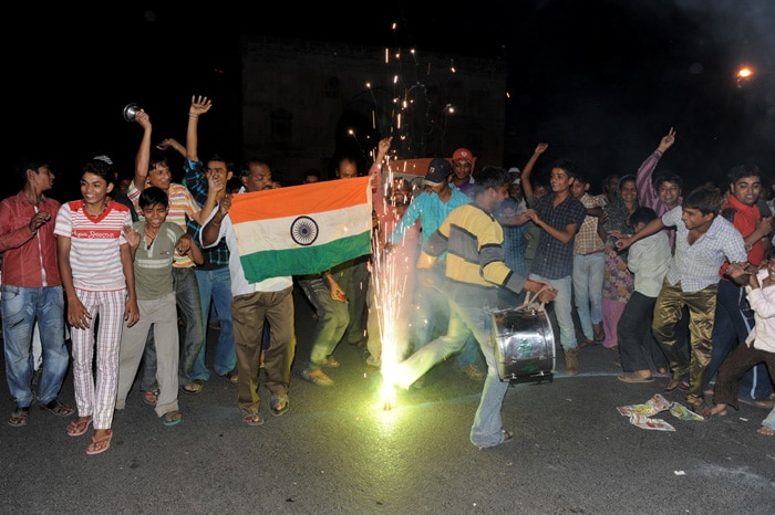 <b>Ahmedabad: </b>Indian cricket fans celebrate with fireworks as they wave flags in a street. (AFP Photo)
