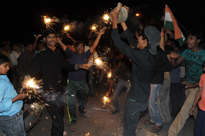 <b>Ahmedabad: </b>Indian cricket fans celebrate with fireworks as they wave flags. (AFP Photo)
