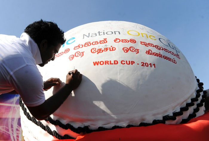 Sri Lankan fans autograph a giant replica cricket ball at a promotional event in Colombo. (AFP Photo)