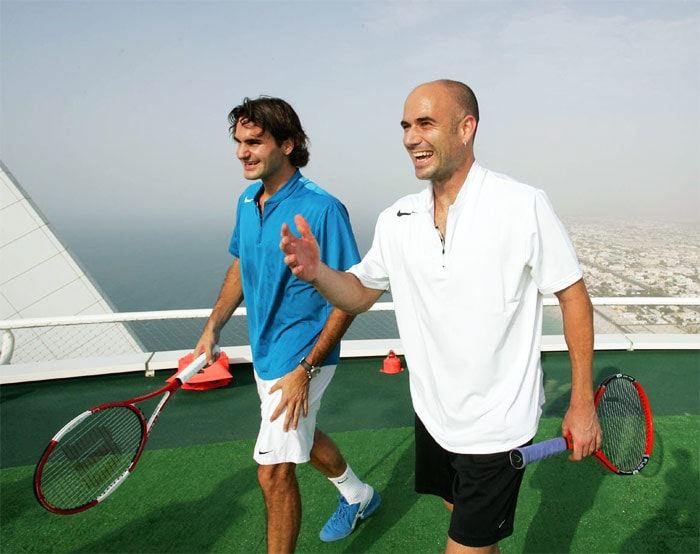 <b>2005</b>: At the start of the year, Federer hired former Australian player Tony Roche to coach him on a limited basis. He reached the Australian Open semi-finals before falling to eventual winner Safin 5–7, 6–4, 5–7, 7–6(6), 9–7. Federer successfully defended his Wimbledon title, winning for the third consecutive year by defeating Roddick in a rematch of the previous year's final, this time winning in straight sets. He then dropped only two sets en route to his second consecutive US Open title, defeating Andre Agassi in four sets in the final. Federer became the first man in the open era to win Wimbledon and the US Open back-to-back in consecutive years (2004 and 2005). In this photo Agassi and Federer are seen playing a friendly at Dubai's Burj Al Arab, home to the world's highest tennis court. (Wikipedia)