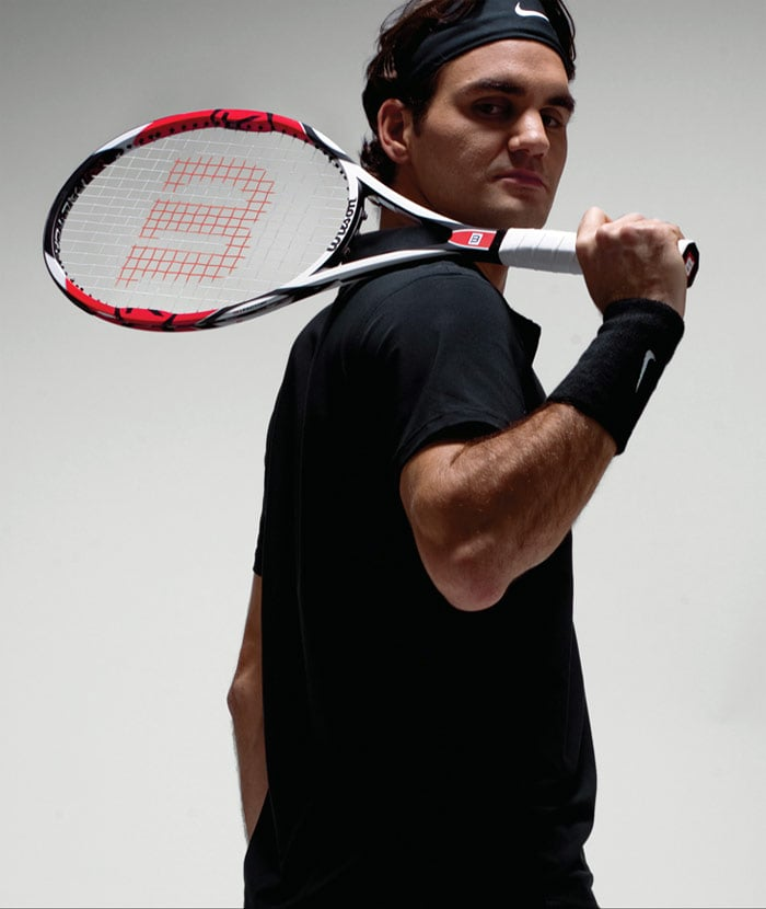 """Federer currently plays with a customised Wilson KFactor KSix-One Tour 90 tennis racquet, which is characterised by its smaller hitting area of 90 square inches, heavy weight of 12.7 ounces, and thin beam of 18 millimeters. His grip size is 4 3/8 inches (sometimes referred to as L3). Federer strings his racquets at 24 to 28 kilograms tension utilizing Wilson Natural Gut 16 gauge for his main strings and Luxilon Big Banger ALU Power Rough 16L gauge (polyester) for his cross strings. When asked about string tensions, Federer stated """"this depends on how warm the days are and with what kind of balls I play and against who I play. So you can see – it depends on several factors and not just the surface; the feeling I have is most important."""" (Wikipedia) (Photo Courtesy: Wilson)"""