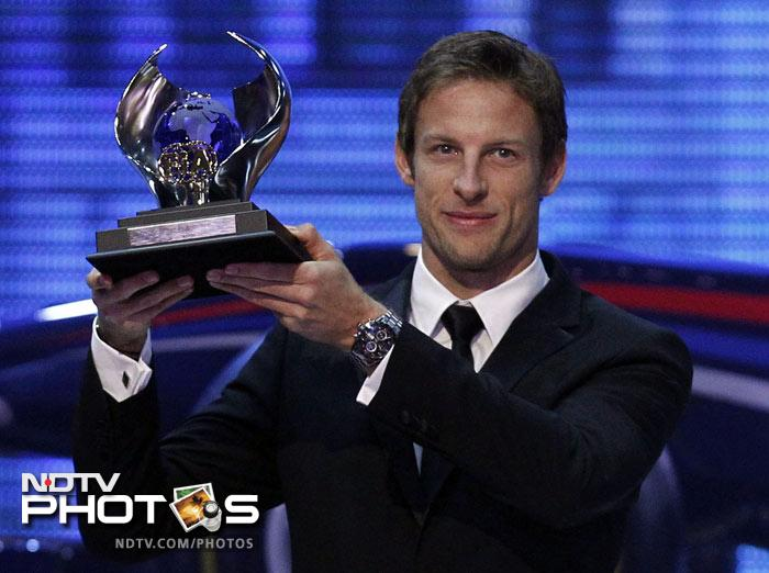 McLaren Formula One driver Jenson Button of Britain poses with his FIA trophy.