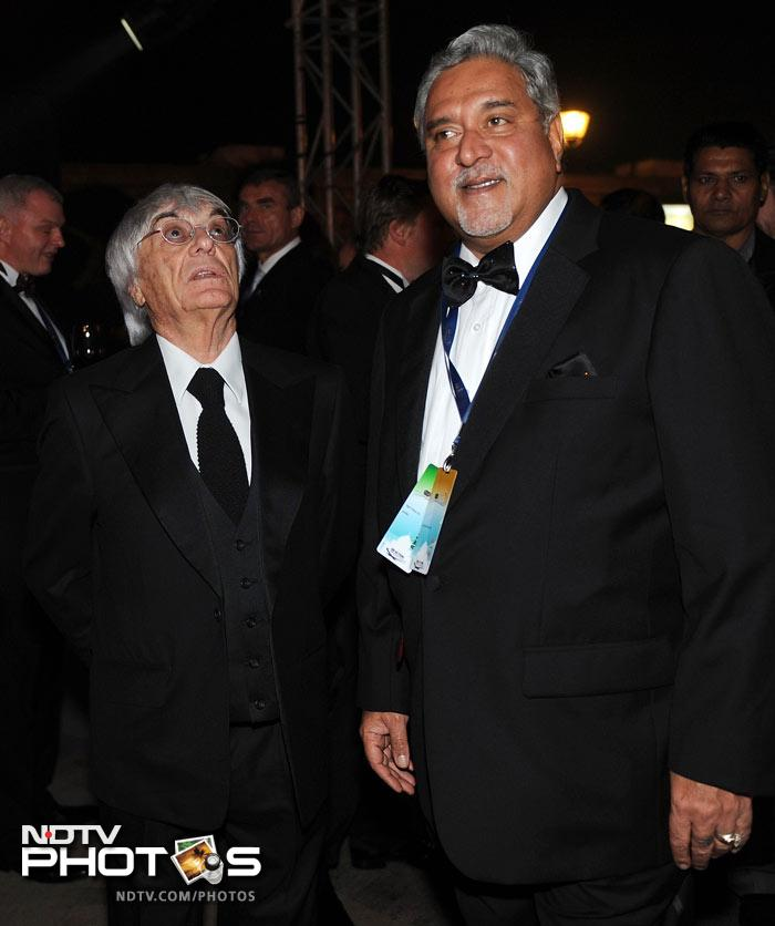 Bernie Ecclestone (L), chief executive officer and president of the Formula One's governing body, interacts with Force India F1 racing team Principal Vijay Mallya during the 2011 FIA Gala night in Gurgaon.