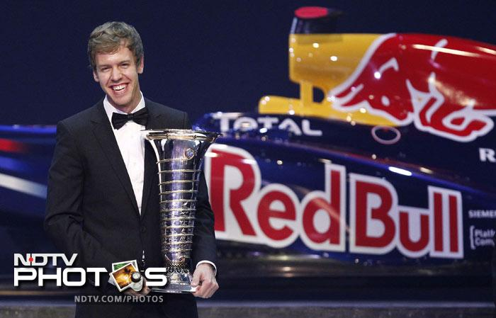 Red Bull Formula One driver Sebastian Vettel of Germany poses with his FIA trophy during the 2011 FIA awards.