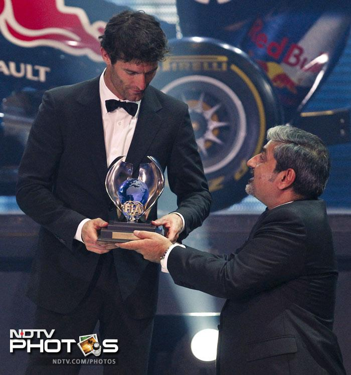 Red Bull Formula One driver Mark Webber (L) of Australia receives his FIA trophy during the 2011 FIA Awards.