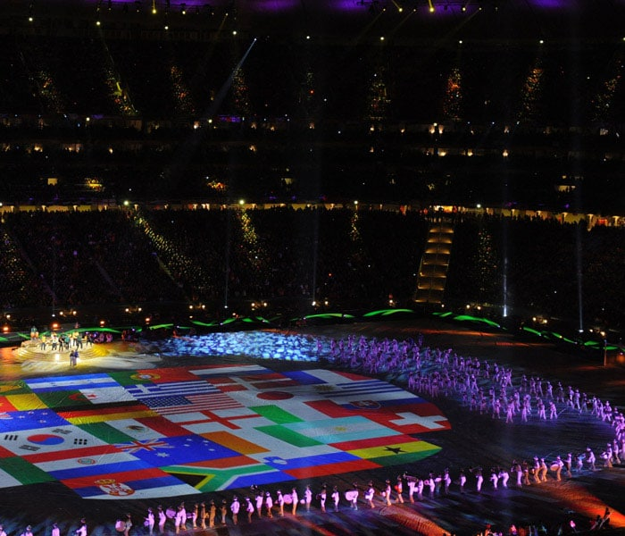 Musicians and singers perform around the flags of all participating teams. (AFP Photo)