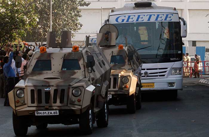 Supporters and onlookers line the road to wave and cheer at a bus transporting India's cricket team, as they are escorted by armored vehicles. (AP Photo)