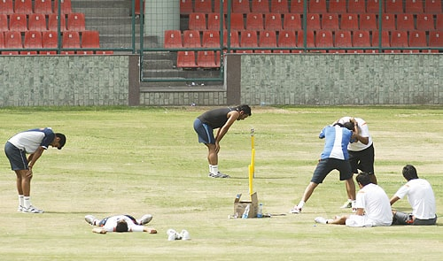 India's Rudra Pratap Singh and Mahendra Singh Dhoni catch their breath after running as Harbhajan Singh in blue wrestles with Praveen Kumar during a fitness test for cricket players in New Delhi. (AP Photo)