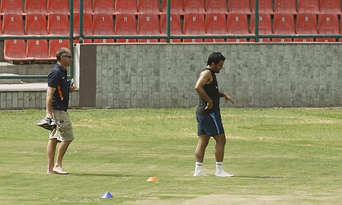 An unidentified support staff carries Mahendra Singh Dhoni's shoes as he walks ahead after a fitness test session in New Delhi. (AP Photo)