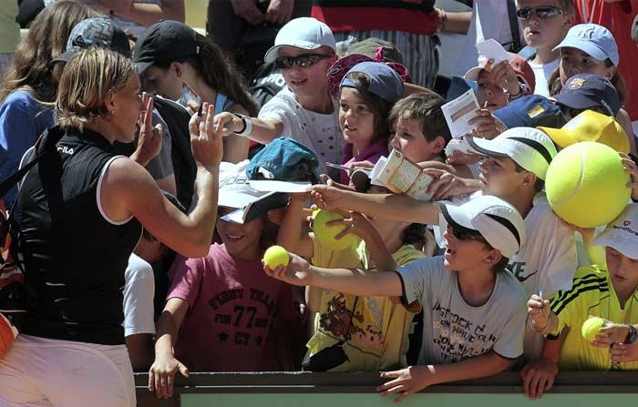 Russia's Svetlana Kuznetsova signs autographs after defeating Irina-Camelia Begu 6-1, 6-1 in a second round match.