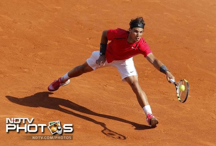 Defending champion Spain's Rafael Nadal returns the ball to Italy's Simone Bolelli during their first round match in the French Open at the Roland Garros stadium in Paris. (AP Photo)