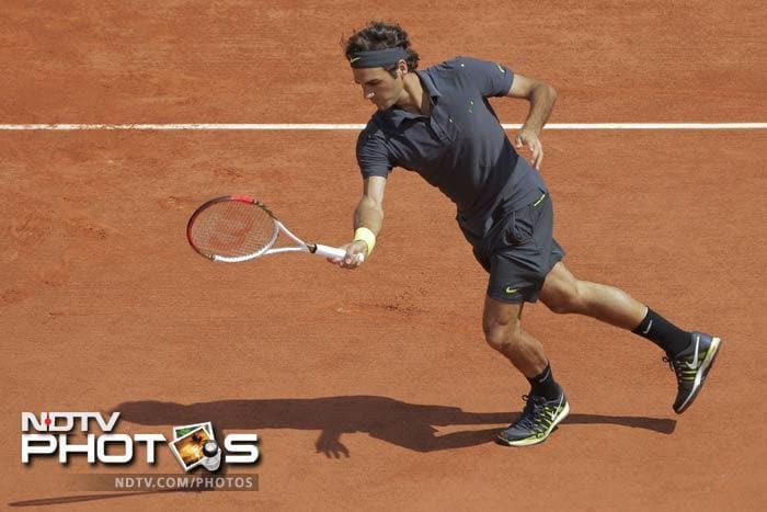 Roger Federer of Switzerland returns in his second round match against Adrian Ungur of Romania at the French Open in Roland Garros stadium in Paris. (AP Photo)