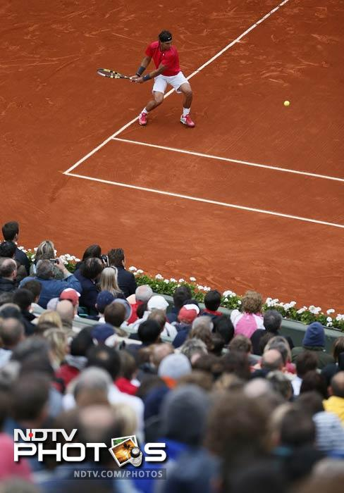 Spain's Rafael Nadal hits a return to Argentina's Juan Monaco during their Men's Singles 4th Round match of the French Open at the Roland Garros stadium in Paris. (AFP Photo)