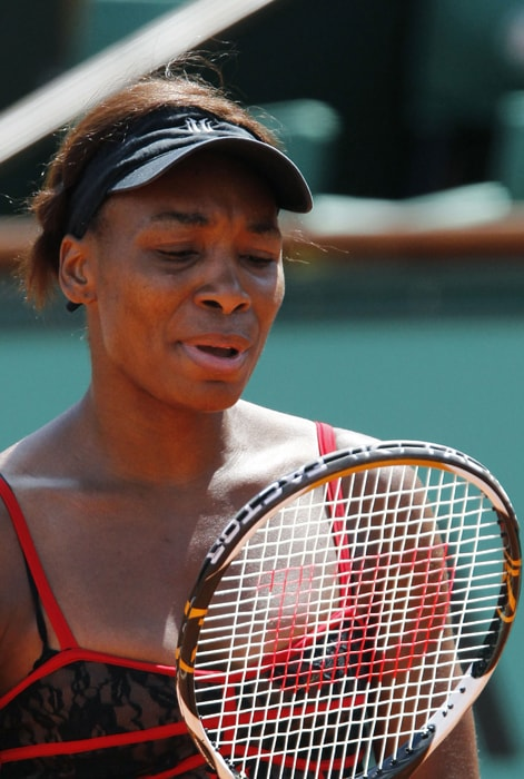 US Venus Williams inspects her raquet during her women's second round match against Slovakia's Dominika Cibulkova in her 6-3, 6-4 win. (AFP photo)