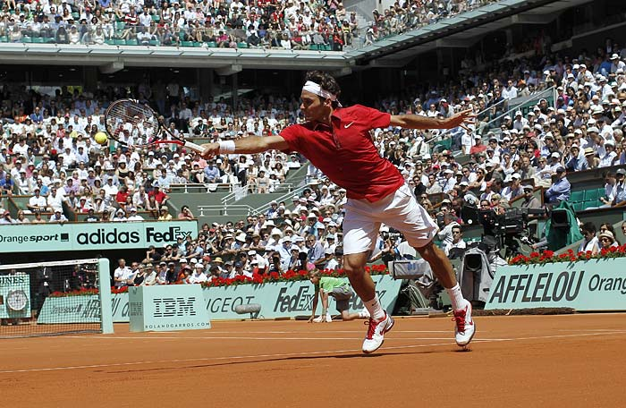 Switzerland's Roger Federer, the winner of the match, returns the ball to Switzerland's Stanislas Wawrinka during their men's fourth round match in the French Open tennis championship at the Roland Garros stadium in Paris. (AFP PHOTO)