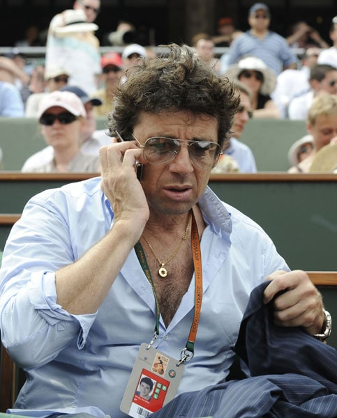 French actor Patrick Bruel speaks on his mobile phone as he watches the action during the the French Open at the Roland Garros stadium in Paris. (AFP Photo)