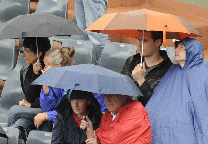 People sit under umbrellas during the men's second round match in the French Open at the Roland Garros stadium in Paris. (AFP Photo)