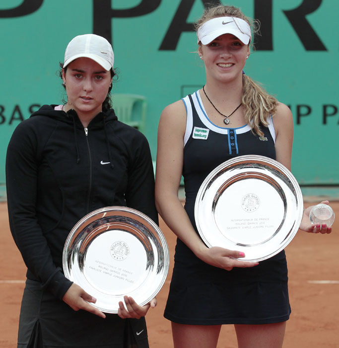 Ons Jabeur of Tunisia holds her runners up trophy as she stands beside winner Elina Svitolina of Ukraine following their Girls Final match in the French Open at the Roland Garros stadium in Paris. (AFP Photo)