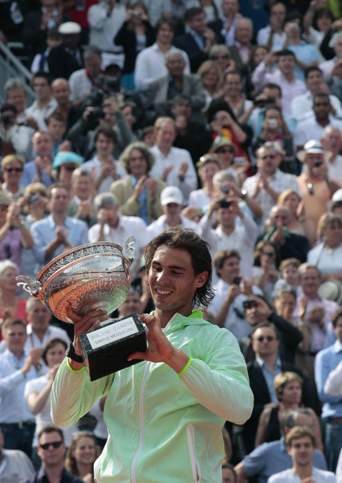 Rafael Nadal holds the winners trophy after beating Robin Soderling following the men's final match in the French Open at the Roland Garros stadium in Paris. (AFP Photo)