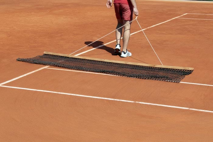An employee prepares the centre court prior to a training session at the Roland Garros tennis stadium in Paris. (AFP Photo)