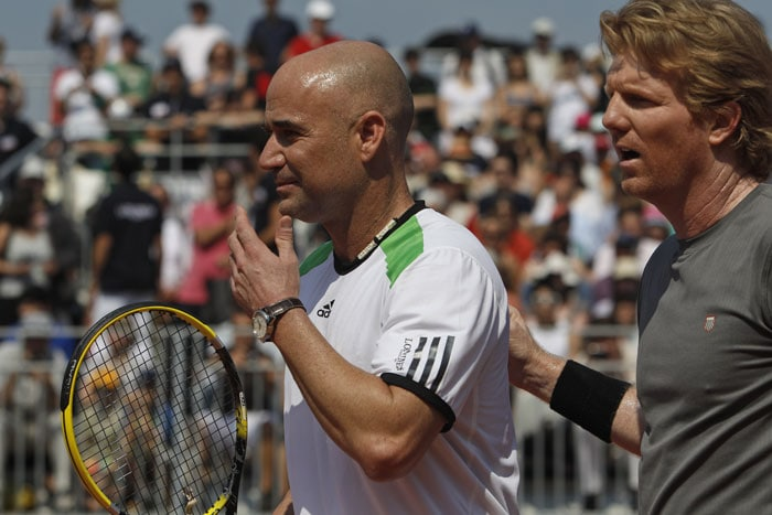 Andre Agassi and Jim Courier of the US play an exhibition match at the French Open tennis tournament in Roland Garros stadium in Paris. (AP Photo)
